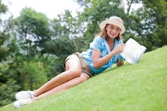 Woman on a grass looking over the book Stock Photography