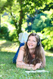 Woman on grass in park reading. Young woman reading book  and  listening music lying on grass in park Royalty Free Stock Images