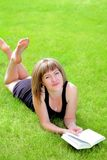 Woman on grass reading Royalty Free Stock Photos