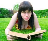 Woman on grass reading a book Stock Photos