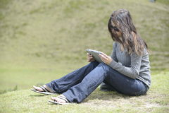 A woman on the grass. A woman is sitting on the grass and reading Stock Photo