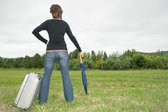 Woman on the grass with suitcase and umbrella Stock Image
