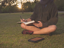 Woman on grass with tablet and notebook in park Royalty Free Stock Photo