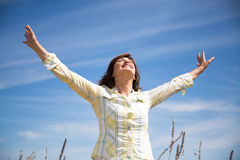 Woman grateful to nature. Attractive middle aged woman enjoying nature with arms raised to the blue sky stock image