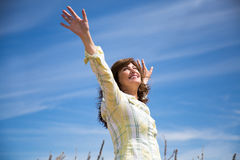 Woman grateful to nature. Attractive middle aged woman enjoying nature with arms raised to the blue sky royalty free stock photography