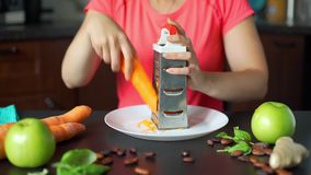 Woman grating carrot in the kitchen. In slow motion. Making a vegetable smoothie process. Healthy lifestyle, weight loss food and nutrition concept stock video footage