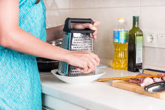 Woman grating cheese on a grater Royalty Free Stock Photography
