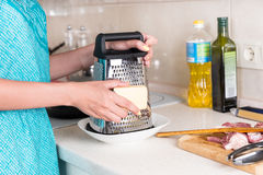 Woman grating a wedge of cheese for a recipe Stock Photography