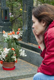 Woman at grave. Sad young woman mourning at grave; profile view royalty free stock photos