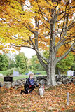 Woman at grave in cemetery. A side view of an elderly woman kneeling at a headstone in a cemetery in Autumn royalty free stock photography