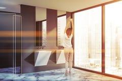 Woman in gray bathroom corner, double sink. Woman in corner of modern bathroom with gray walls, marble floor, loft window, white double sink with two vertical stock image