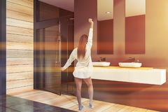 Woman in gray bathroom corner with shower. Woman in pajamas standing in modern bathroom interior with gray and wooden walls, tiled floor, double sink and shower royalty free stock images