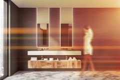 Woman in gray bathroom with double sink. Woman in interior of modern bathroom with gray walls, marble floor, loft window, double sink with two vertical mirrors stock photography