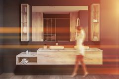 Woman in gray bathroom with double sink. Woman walking in modern bathroom interior with gray walls, tiled floor and white double sink standing on wooden royalty free stock photography