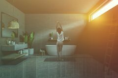 Gray bathroom, tub and sink, ladder, woman. Woman in gray bathroom interior with concrete floor, white bathtub, long gray sink with horizontal mirror above it royalty free stock images
