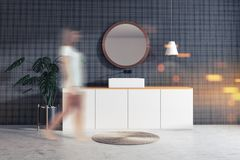 Woman in gray bathroom with sink and round mirror. Woman in interior of modern bathroom with gray tile walls, concrete floor, sink standing on white countertop royalty free stock images
