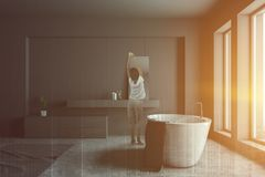 Woman in gray bathroom with tub and sink. Rear view of woman in pajamas standing in modern bathroom interior with gray walls, concrete floor, white bathtub and royalty free stock photography