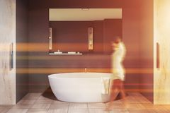 Woman in gray bathroom with white tub. Woman walking in gray wall bathroom interior with tiled floor, round bathtub and horizontal mirror hanging above it. Toned stock images