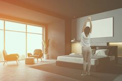 Woman in gray bedroom corner. Woman in pajamas standing in stylish bedroom corner with gray and white walls, concrete floor, master bed with poster above it and royalty free stock images