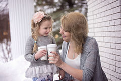 Woman in Gray Cardigan With Girl in Grey Sweater Both Holding White Paper Cup With White Concrete Column and Trees in the Backgrou Royalty Free Stock Photography