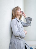 Woman in gray cloak calling on the phone Stock Photo