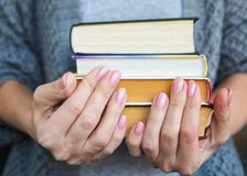 The woman in gray clothes holds four books in hand. royalty free stock photos