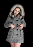 Woman in gray coat on black background Stock Photos