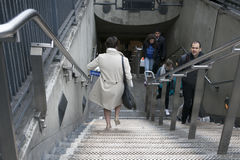 A woman in a gray coat and heels down the stairs in the tube, holding a box marked Legacy Stock Images