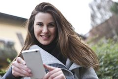 Woman in Gray Coat Holding White Smartphone Stock Images