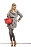 Woman in gray coat holds red handbag Stock Photo