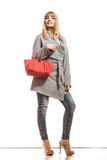 Woman in gray coat holds red handbag Stock Photos
