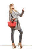 Woman gray coat red handbag showing copy space Royalty Free Stock Image