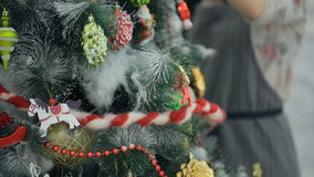 Woman in a gray dress is decorated artificial Christmas tree. stock video