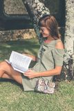 Woman in Gray Dress Reading Book at Daytime Royalty Free Stock Photos