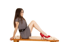 Woman gray dress red shoes sit side. A woman sitting on a bench in her gray sweater dress, wearing a red shoes Stock Image