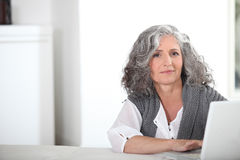 Woman with gray hair. And computer royalty free stock photo