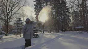 A woman in a gray hat and a gray down jacket pours boiling water from a transparent bucket in the frost winter park stock video footage