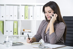 Woman in gray on her phone. Portrait of a woman in gray on her phone. She is talking and taking notes in her clipboard. Concept of sales work Royalty Free Stock Photos