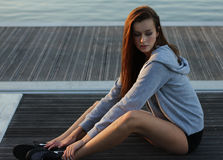 Woman in Gray Hoodie and Black Shorts Sitting on Black Wooden Dock Near Ocean Water Under Sunny Sky Royalty Free Stock Photo