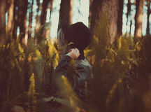Woman in Gray Jacket Holding Black Fedora Near Brown Tree during Daytime Stock Photos
