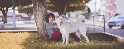 Woman in Gray Long Sleeve Top and Red Pants Sitting Beside Tree and White Medium Coated Dog Stock Photo