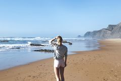 Woman in Gray Long-sleeved Shirt With Pink Short Shorts Standing Near Sea stock image