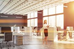 Woman in gray open space office. Blonde businesswoman standing in open space office with gray walls, concrete floor and rows of white and wooden computer desks royalty free stock photography
