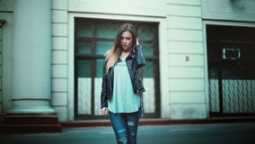 Woman in Gray Printed Shirt With Black Leather Jacket and Black Distressed Jeans royalty free stock images