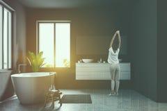 Woman in gray Scandinavian bathroom interior. Woman in Scandinavian bathroom interior with gray walls, a concrete floor, large windows and a white bathtub stock photography