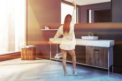 Woman in gray Scandinavian style bathroom corner. Woman in Scandinavian style bathroom corner with grey walls, a white wooden floor, a sink with a large mirror stock photo