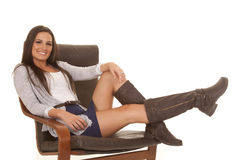 Woman gray shirt sit legs up out Royalty Free Stock Photos