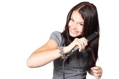 Woman in Gray Shirt Straightening Her Hair Stock Images