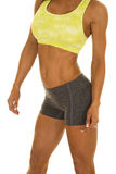 Woman gray shorts and green sports bra body side Stock Image