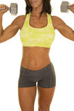 Woman gray shorts and green sports bra flex weights body. A close up of a woman working out with weights Royalty Free Stock Photos